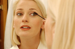 Woman putting on mascara in bathroom mirror 1.jpg