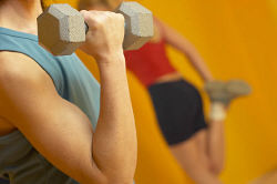 Mature adult woman lifting weights with woman stretching in background uid 1427320.jpg